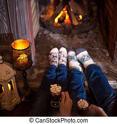 Couple relaxing at home drinking cocoa. Feet in wool socks ...