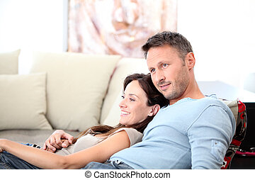 Couple relaxing at home in front of tv