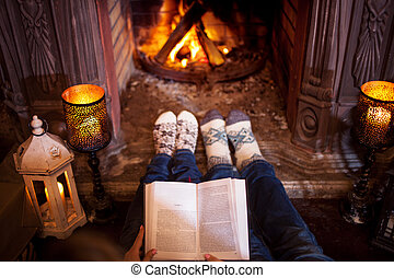 Couple relaxing at home reading a book. Feet in wool socks ...