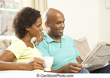 Couple Relaxing At Home With Newspaper