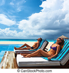 Couple relaxing at the poolside - Couple relaxing in chaise...
