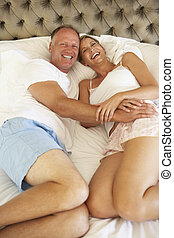 Couple Relaxing In Bedroom