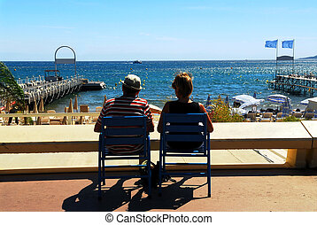 Couple relaxing in chairs in Cannes - Couple relaxing in...