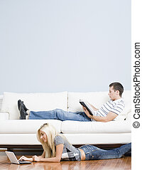 Couple Relaxing in Living Room - Man reads on a couch while...