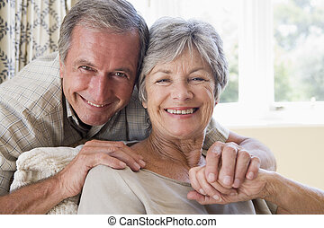 Couple relaxing in living room smiling