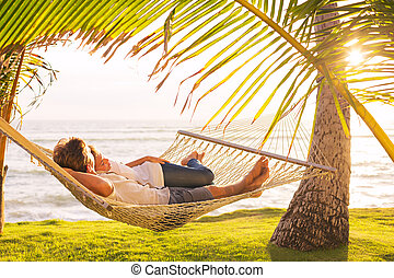 Couple relaxing in tropical hammock - Romantic couple ...