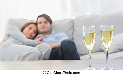 Couple relaxing on a couch with flutes of champagne