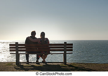 Couple Relaxing on a Ocean View Bench