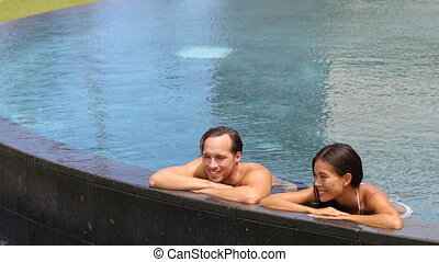 Couple relaxing together in swimming pool on vacation