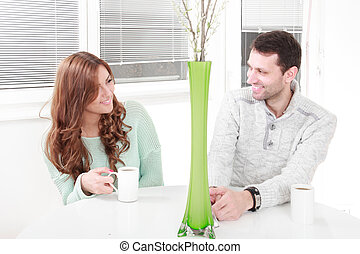 Romantic young happy couple in love sitting at home resting