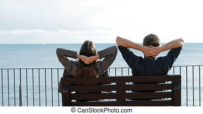 Couple relaxing watching ocean in a bench
