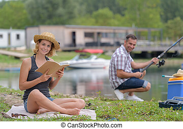 couple relaxing while fishing at the lake