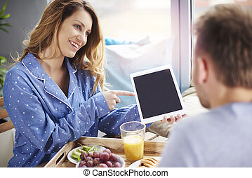 Couple relaxing with digital tablet during breakfast