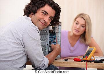 Couple repairing computer