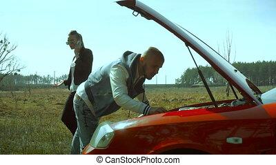 couple repairs broken car in the field