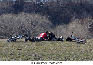 Couple resting in the park with bicycles lying