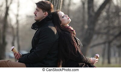 Couple resting on a park bench, leaning against each other backs