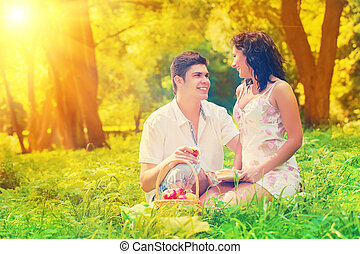 couple resting on grass in park