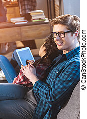 couple resting on sofa, using tablet