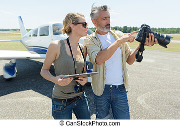 couple reviewing photos on professional camera at airport