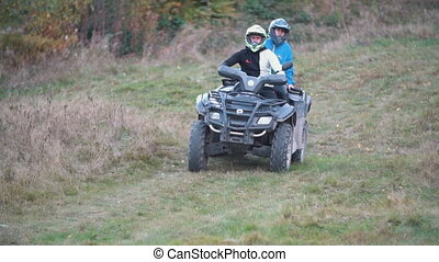 couple ride a quad bike