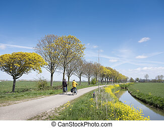 couple rides bicycle in dutch countryside under blue sky in spring