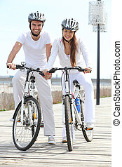 couple riding bicycle wearing cycle helmet