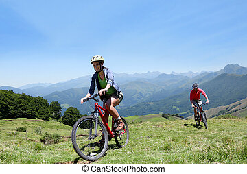 Couple riding bicycles in the mountains
