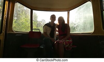 Couple riding in a tram through the forest