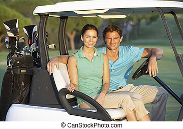 Couple Riding In Golf Buggy On Golf Course