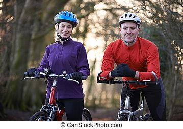 Couple Riding Mountain Bikes Through Woodlands