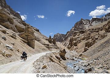 Couple riding on bike among jagged mountains