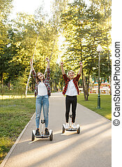 Couple riding on gyro board in park, eco transport