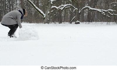 couple roll snowball - couple woman man roll snowball snow...