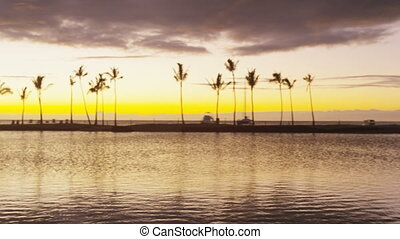 Couple romantic at sunset walking in love enjoying honeymoon vacation at night talking together laughing in casual clothing at beach lagoon on Big Island, Hawaii, USA. Interracial couple.