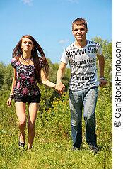 Couple run on grass