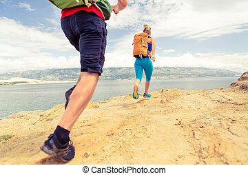 Couple runners running with backpacks on rocku trail at seaside