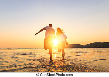 couple running and hand hold on the beach between sunset.