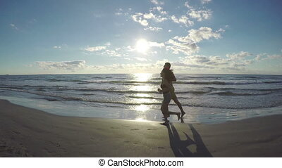 Couple running and kissing on the beach by the sea