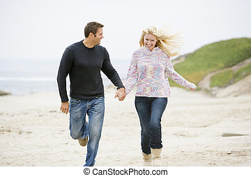 Couple running at beach holding hands smiling
