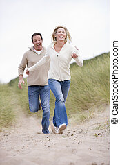 Couple running at beach smiling