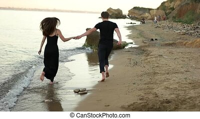 Couple running barefoot on the beach