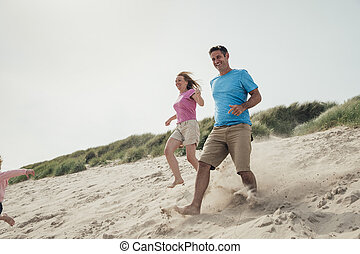 Couple Running Down a Sand Dune