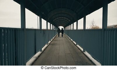 Couple running hand-to-hand across the footbridge over highway