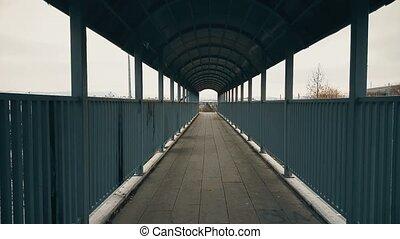 Couple running hand-to-hand across the footbridge over highway