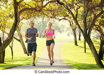 Couple running in park - Couple jogging running outside in...
