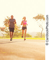 Couple running in the park at sunrise