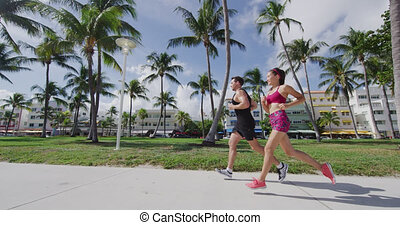 Couple running jogging exercising on South Beach, Miami, Florida, in Art Deco District. Man and woman runners working out together. Lifestyle video in SLOW MOTION shot on RED Cinema Camera.