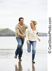 Couple running on beach smiling