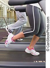 Couple running on treadmills at gym